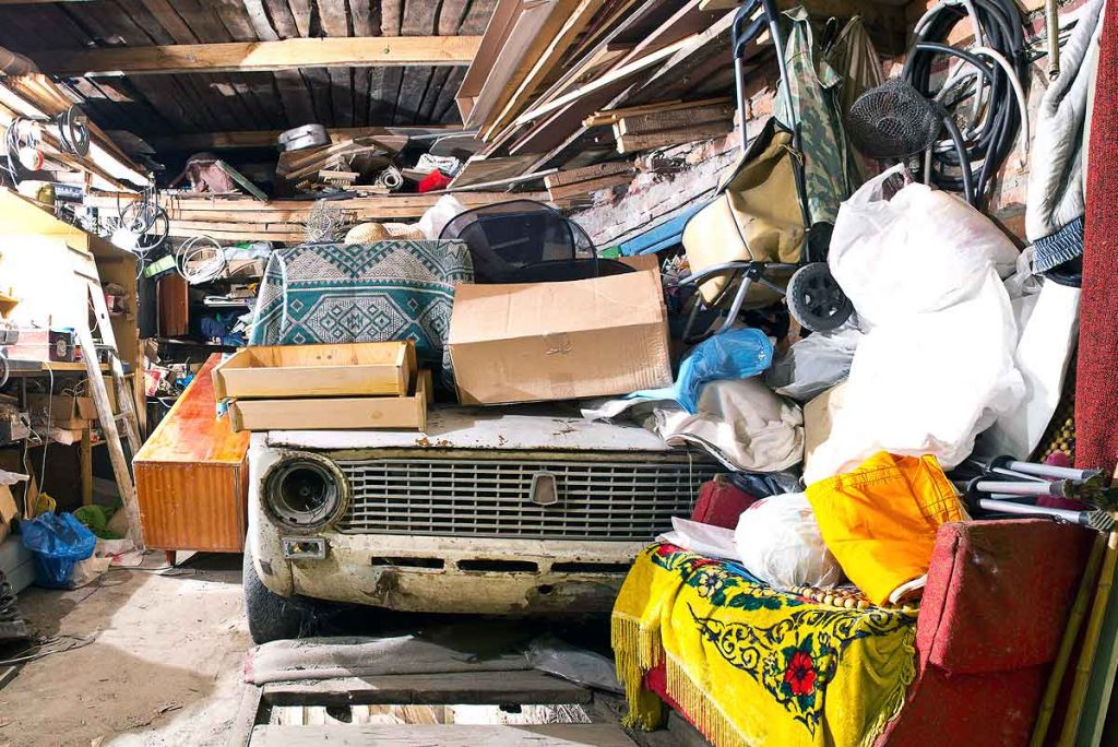 Junk car in garage surrounded by junk and garbage - Spring Cleaning Tips When Clearing Out Your Garage in Philadelphia