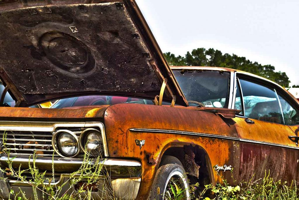 Abandoned Junk and Rusted Car in Field in Philadelphia